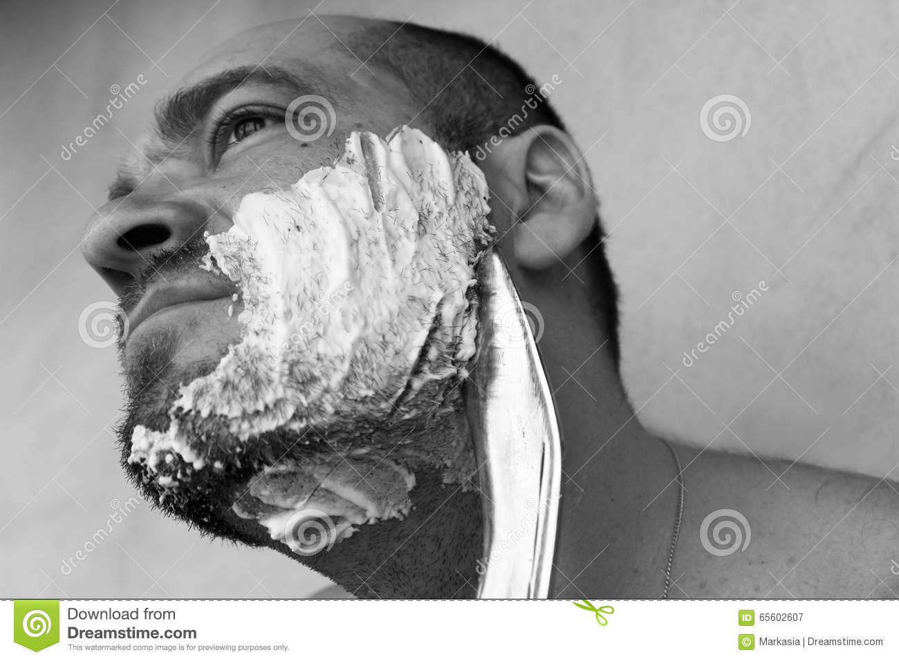 Man shaves his beard with a knife