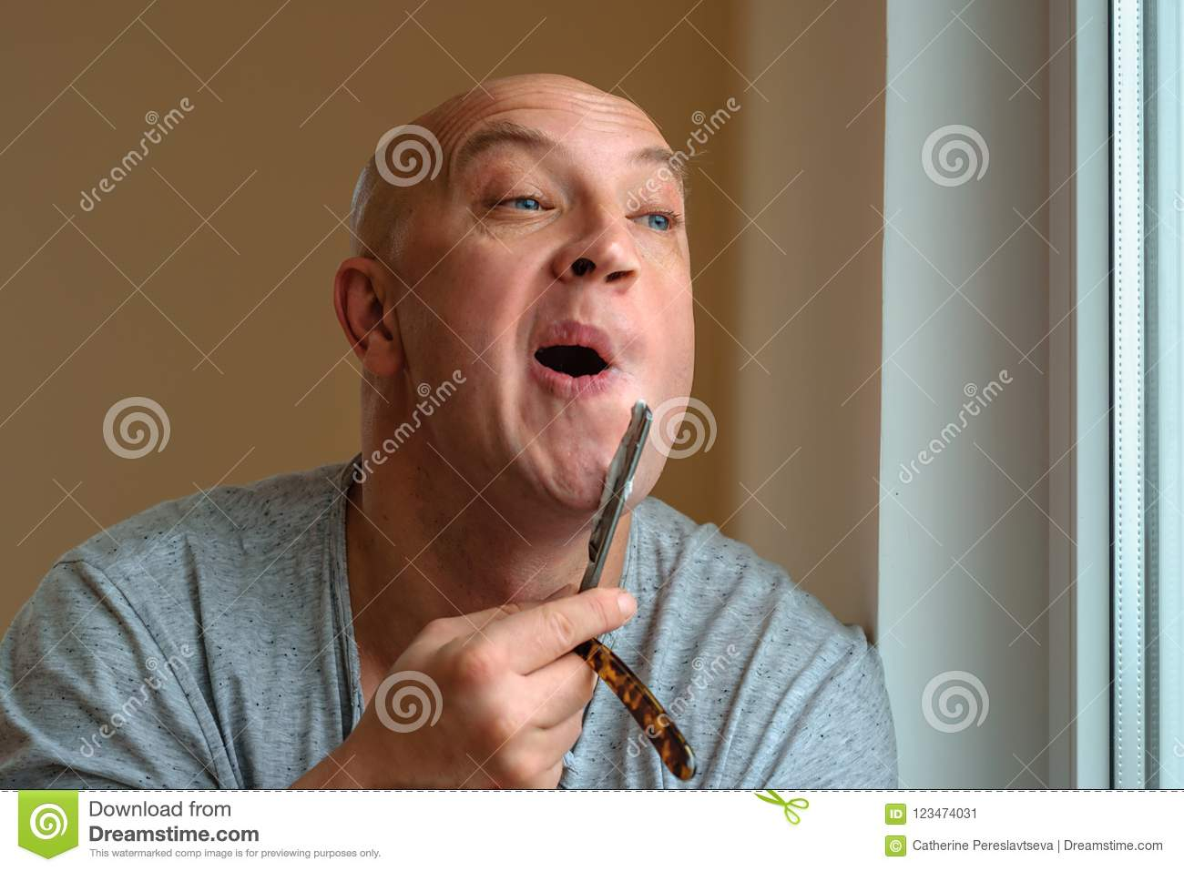 A man shaves with a straight razor