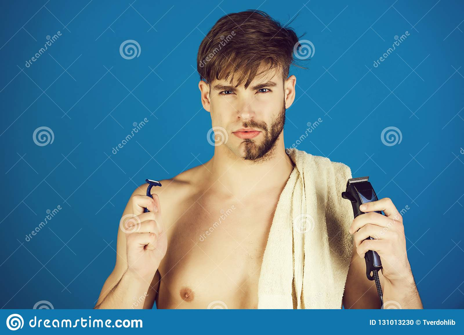 Man shaving face hair, beard, moustache with safety razor and electric  shaver with towel on naked shoulder on blue background. Innovation,  archaism.