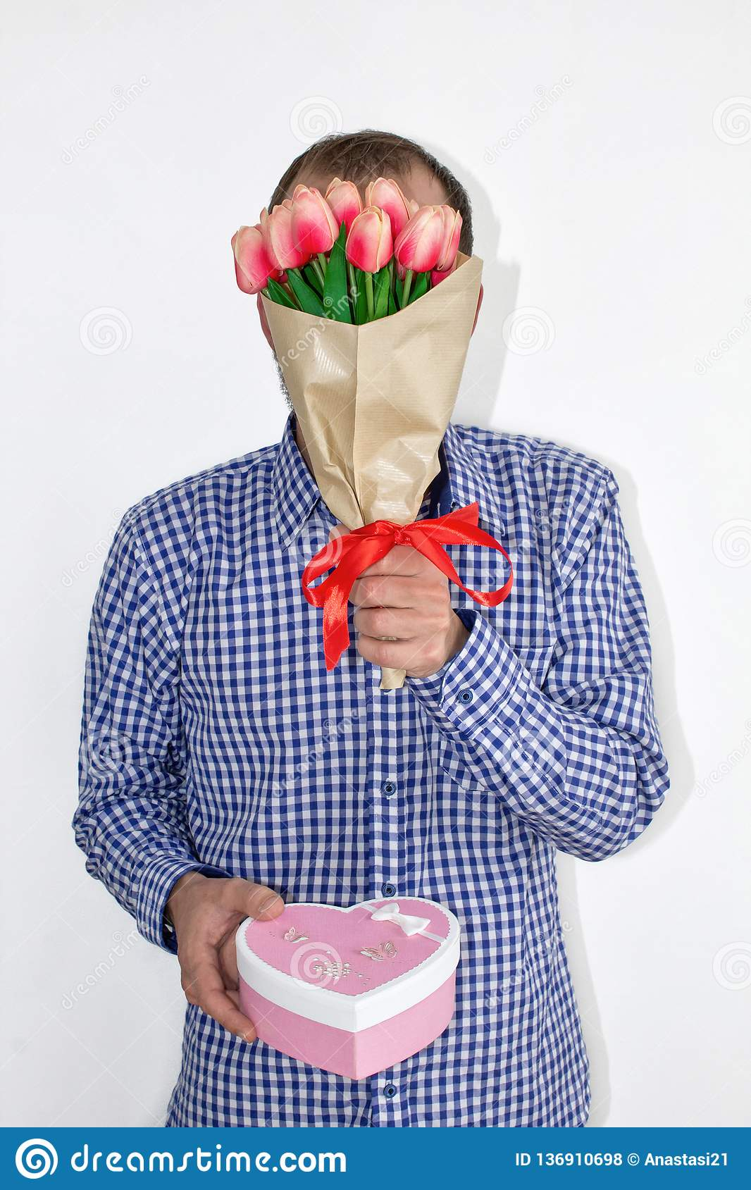 A man in a shirt holds tulips flowers in front of his face and holds out a heart-shaped box on a white background.