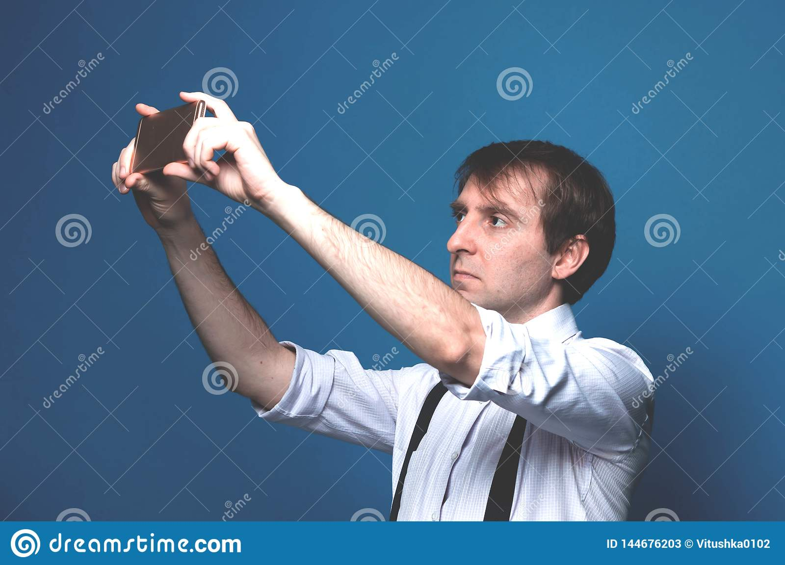 Man in shirt with rolled up sleeves and black suspender standing and taking selfie on blue background