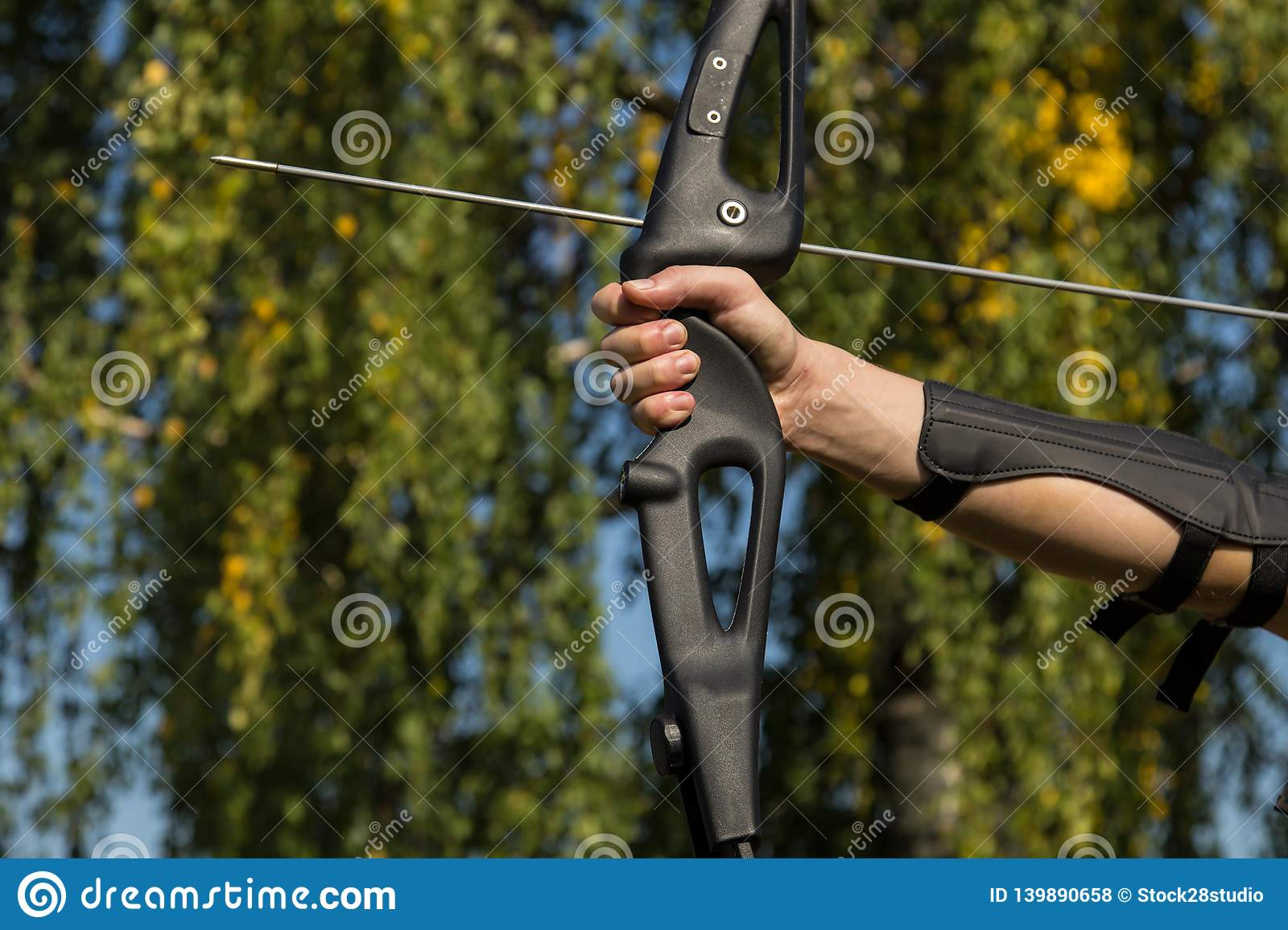 The man shoots from the bow. Close-up. Practice of archery