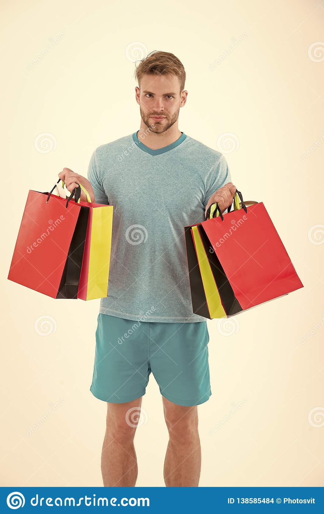 Man with shopping bags isolated on white. Macho with colorful paper bags. Fashion shopper in casual blue tshirt and