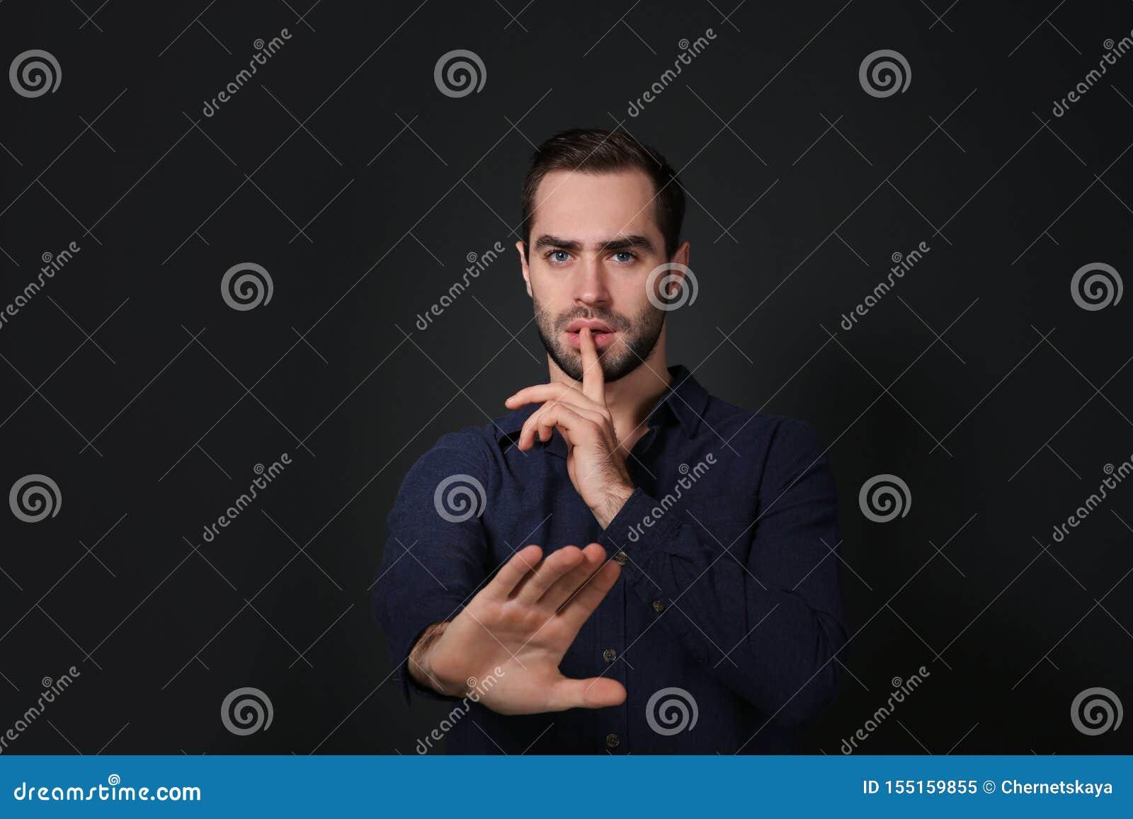 Man showing HUSH gesture in sign language on black