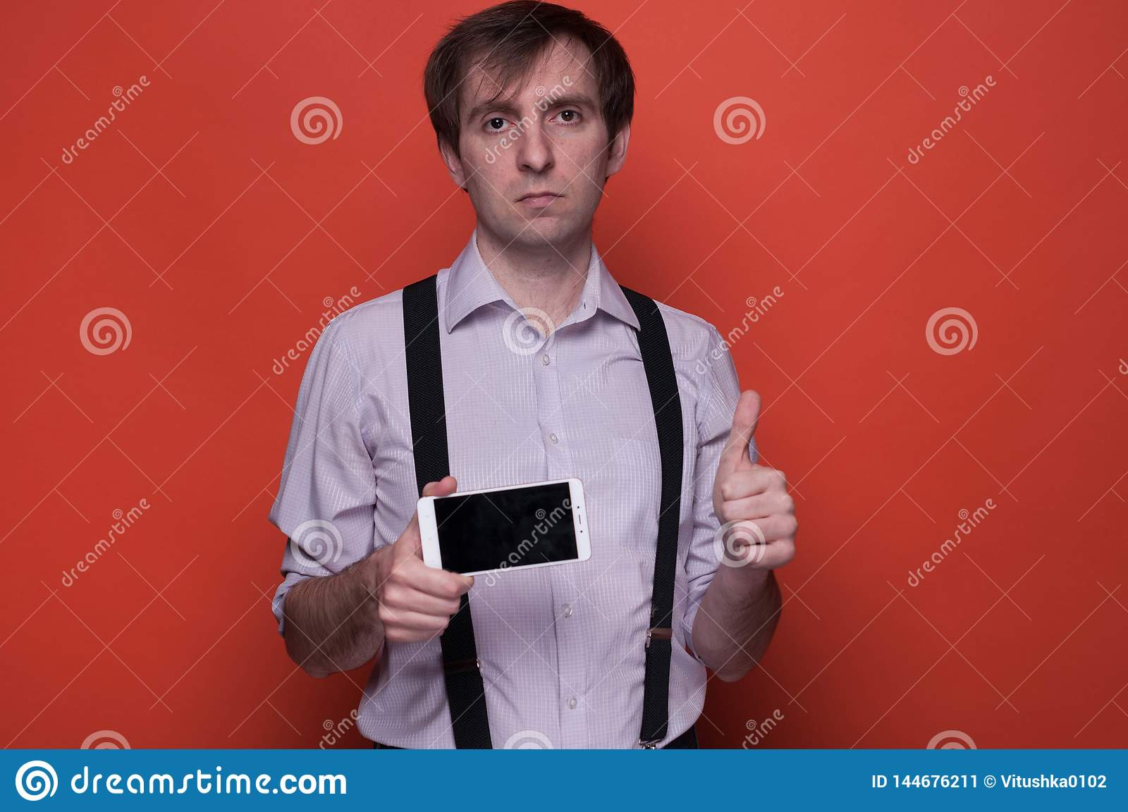 Man showing smartphone with blank screen and thumbing up