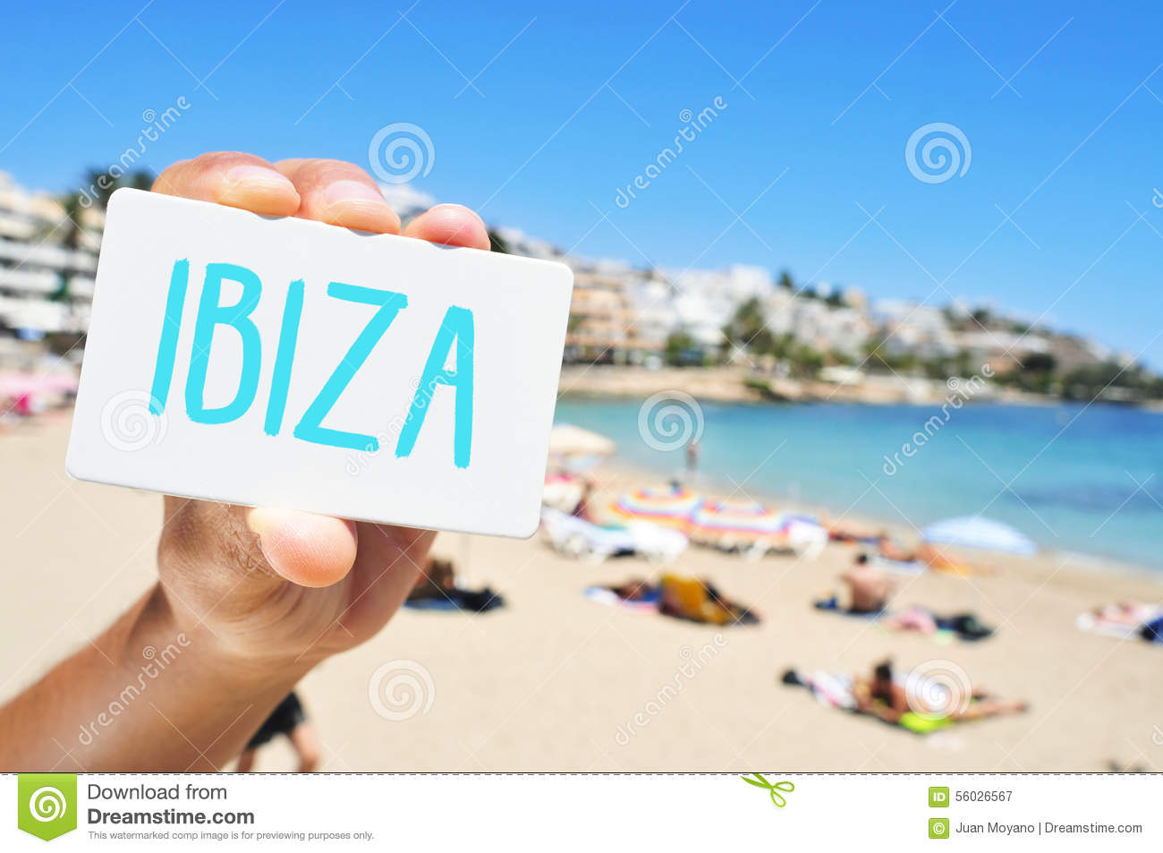 man with a signboard with the word Ibiza, in Ses Figueretes Beach in Ibiza Town, Spain