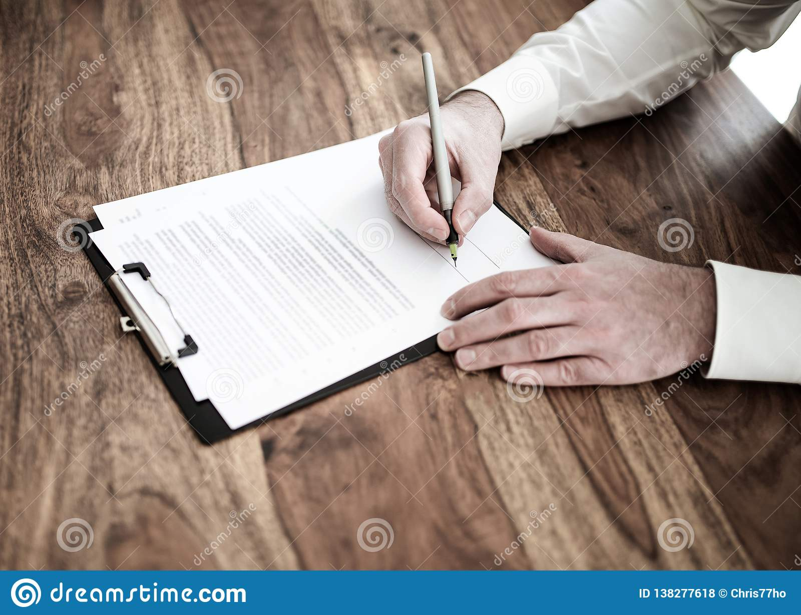 Man signing contract or document at wooden desk