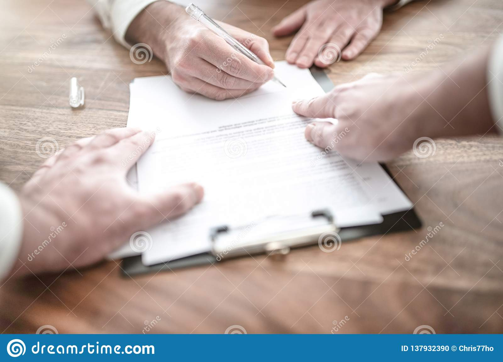 Man signing contract at wooden desk with other person pointing at document
