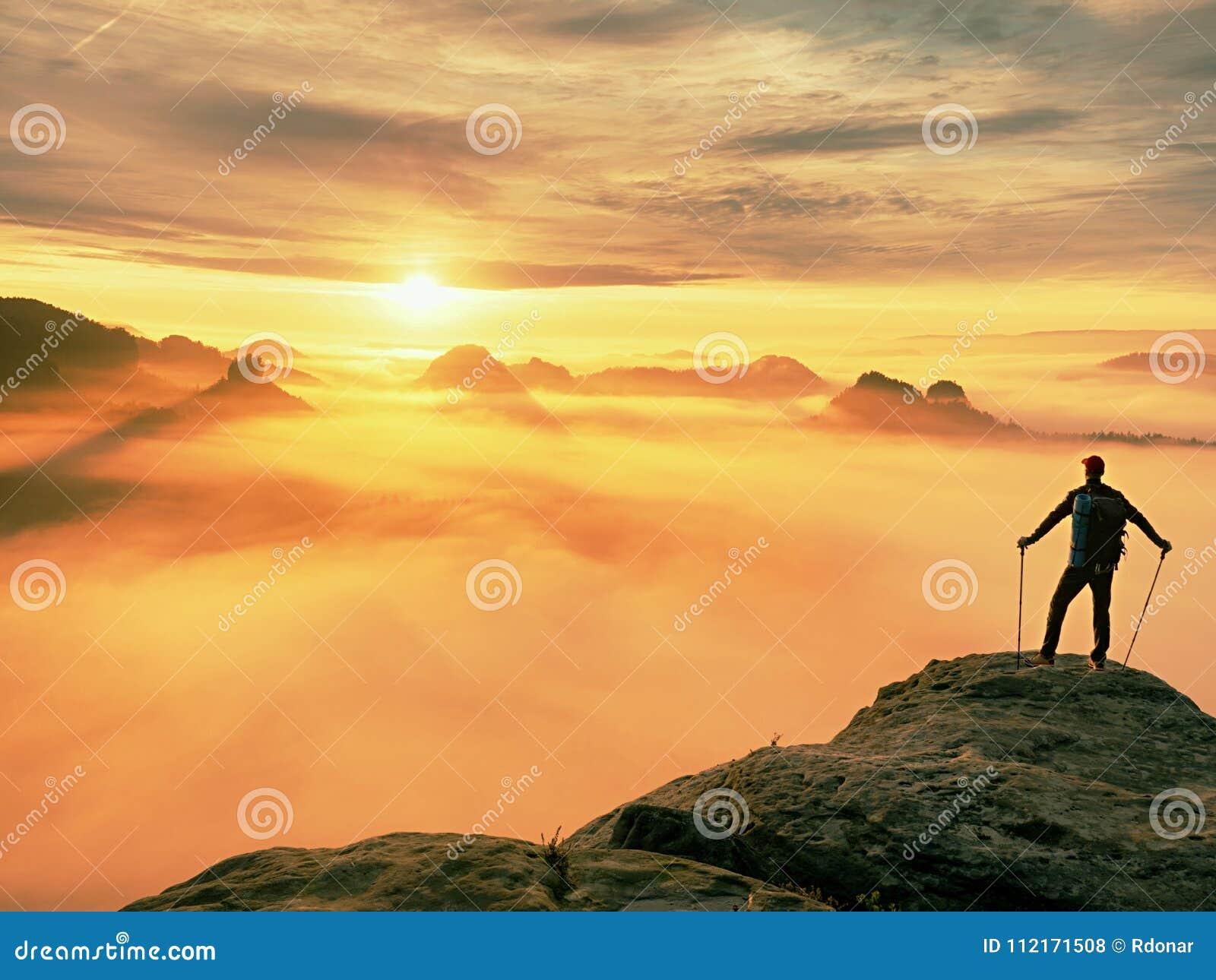 Man silhouette stay on sharp rock peak. Satisfy hiker enjoy view. Tall man on rocky cliff