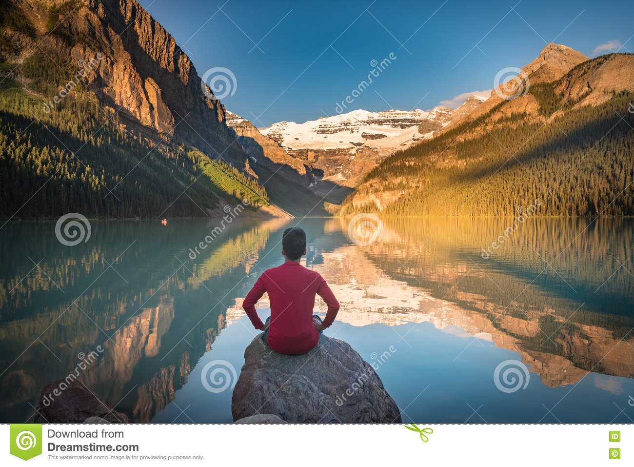 Man sit on rock watching Lake Louise reflections