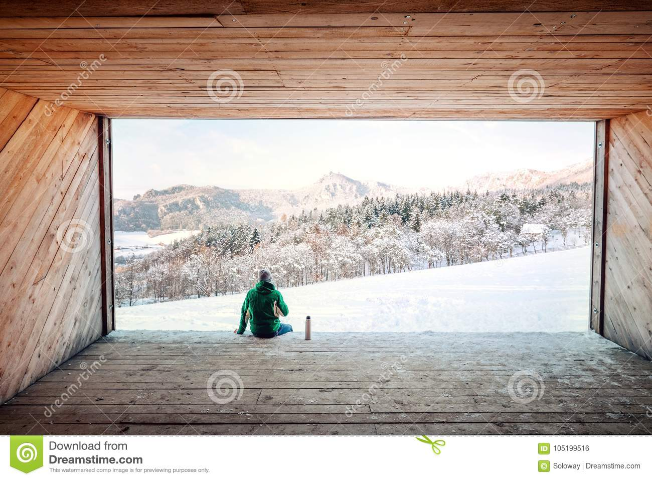 Hangar Camping Car man sits in wooden hangar wit view on snowy mountain valley stock