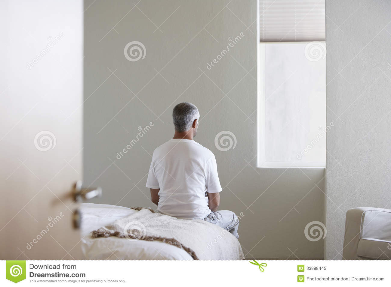 Man Sitting On Bed In Bedroom Royalty Free Stock Photo