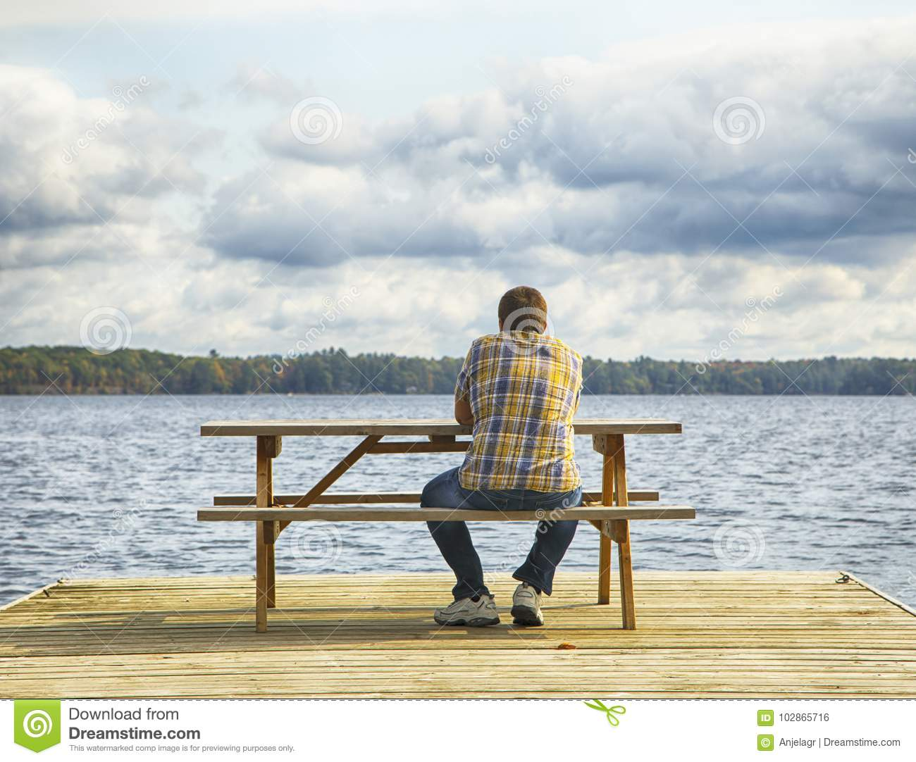Man sitting on a bench in front of a lake