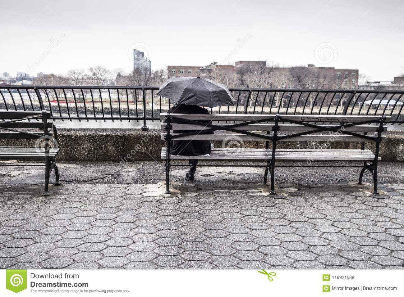 Man sitting on bench with umbrella in a water way park