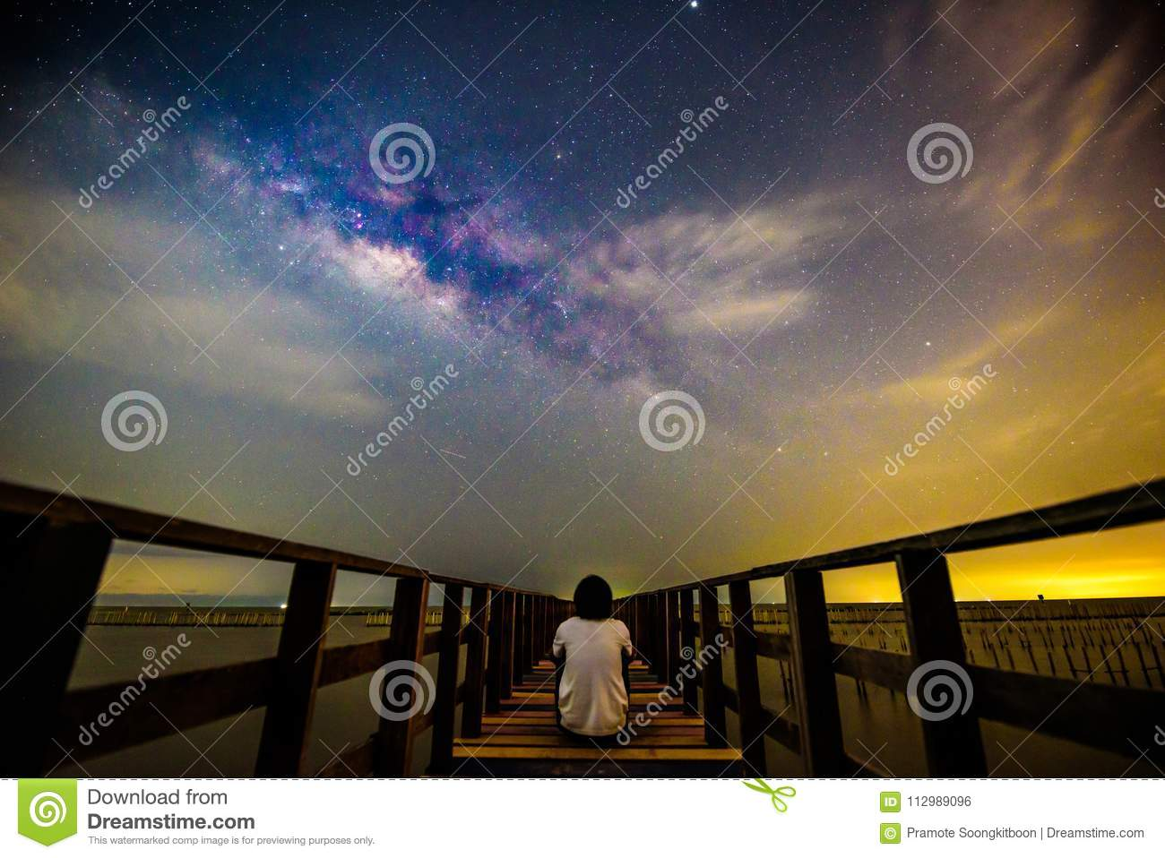 The man sitting at the bridge with milky way