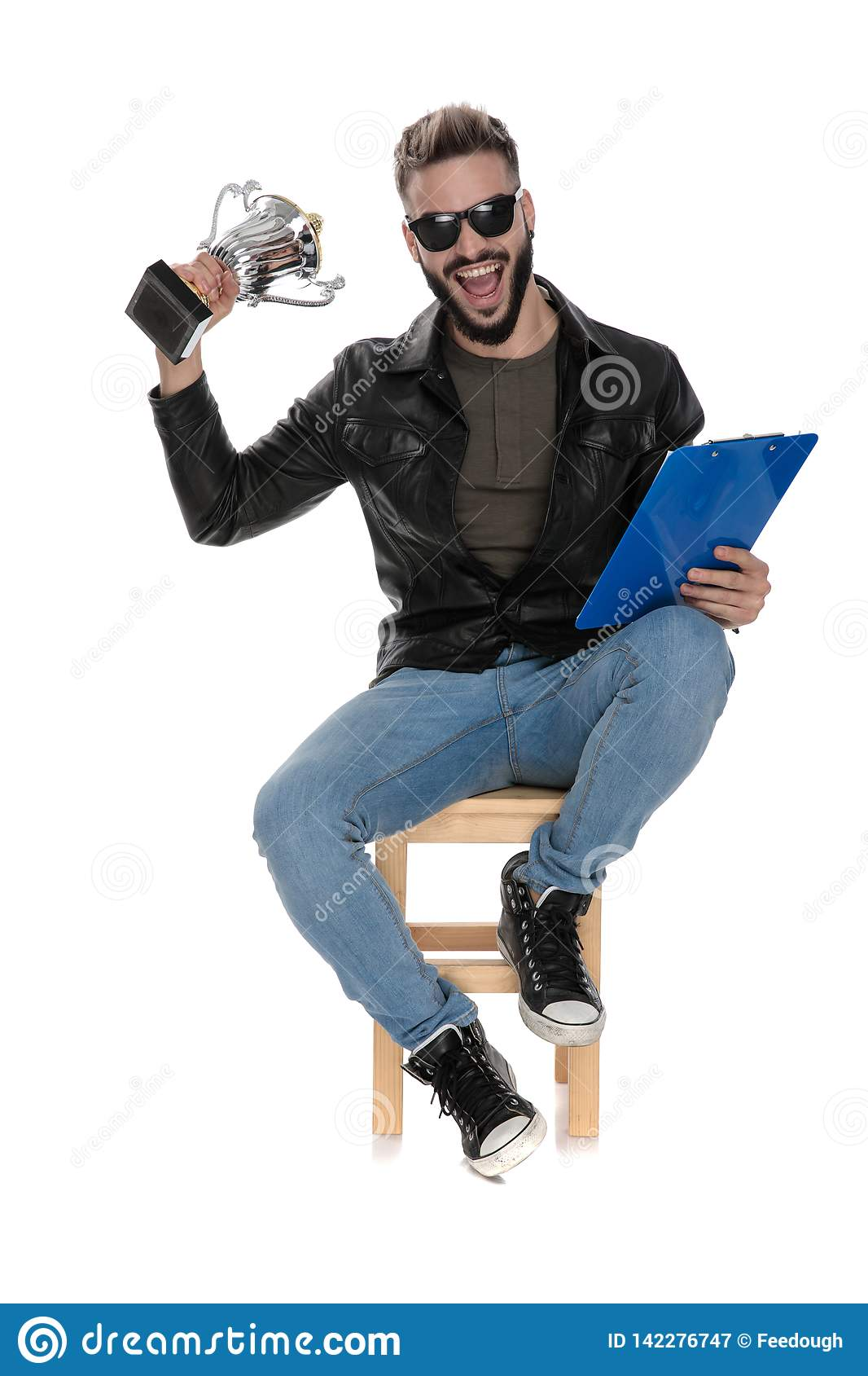 Man sitting on chair holding trophy and blue folder