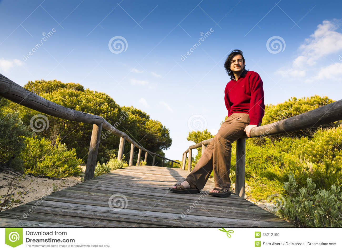 Man sitting on a coastal boardwalk