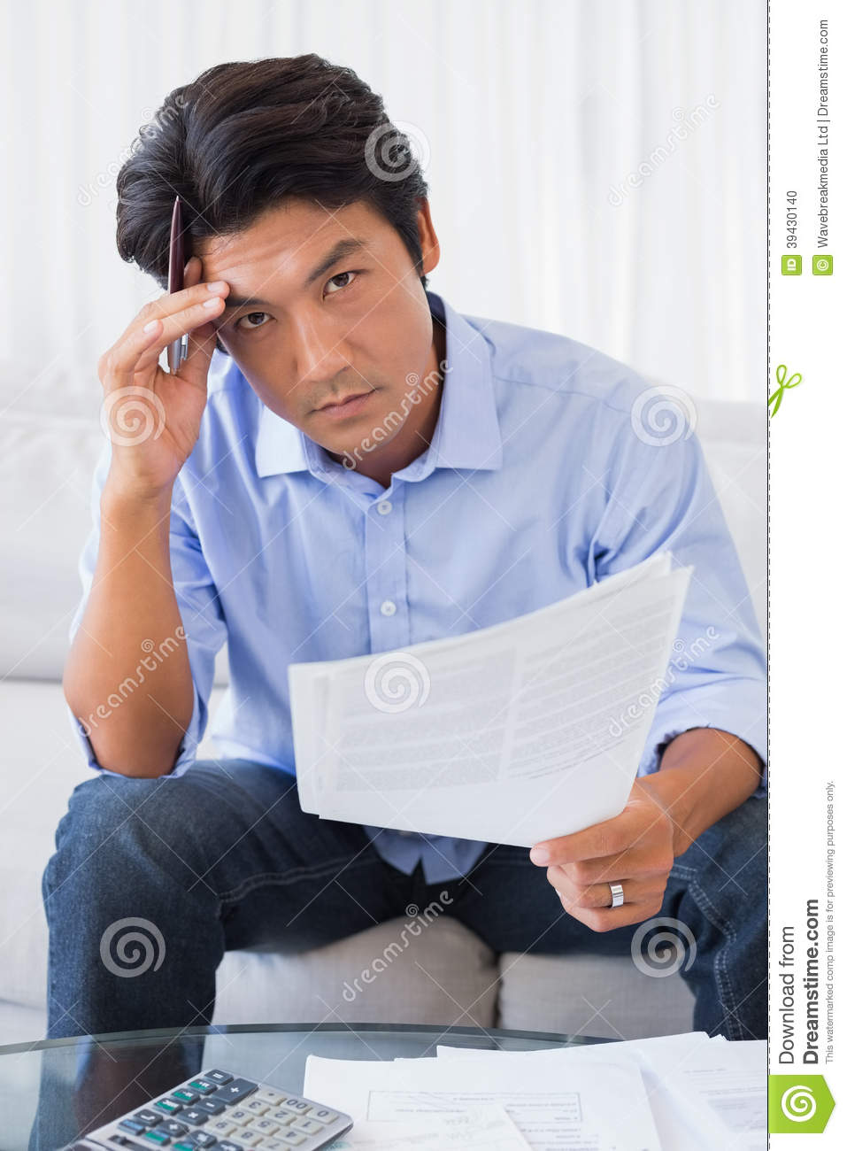 Man Sitting On Couch Working Out His Finances Stock Photo