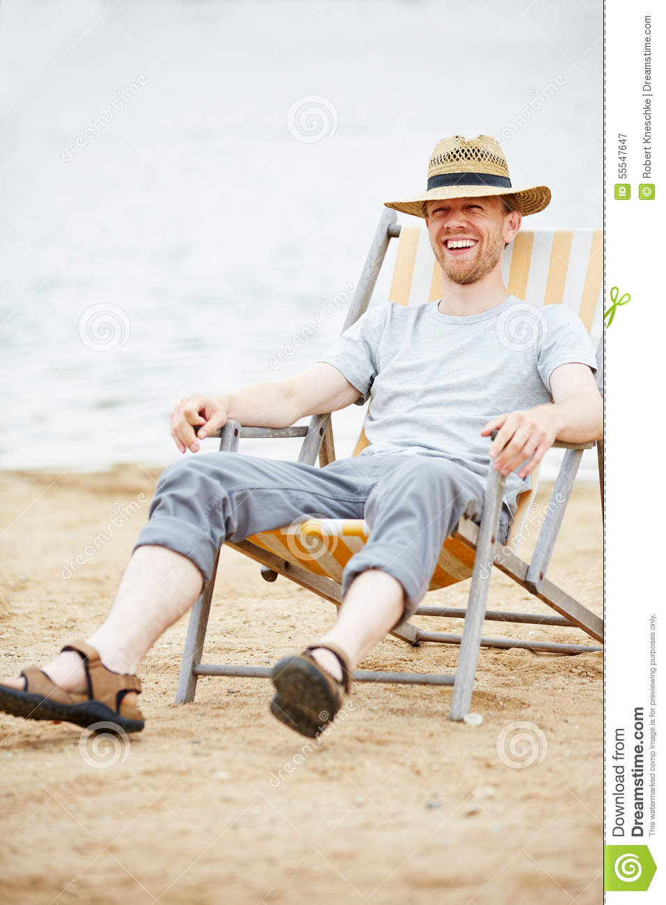47975e9fbe Man Sitting In Deck Chair On Beach Stock Image - Image of deck ...