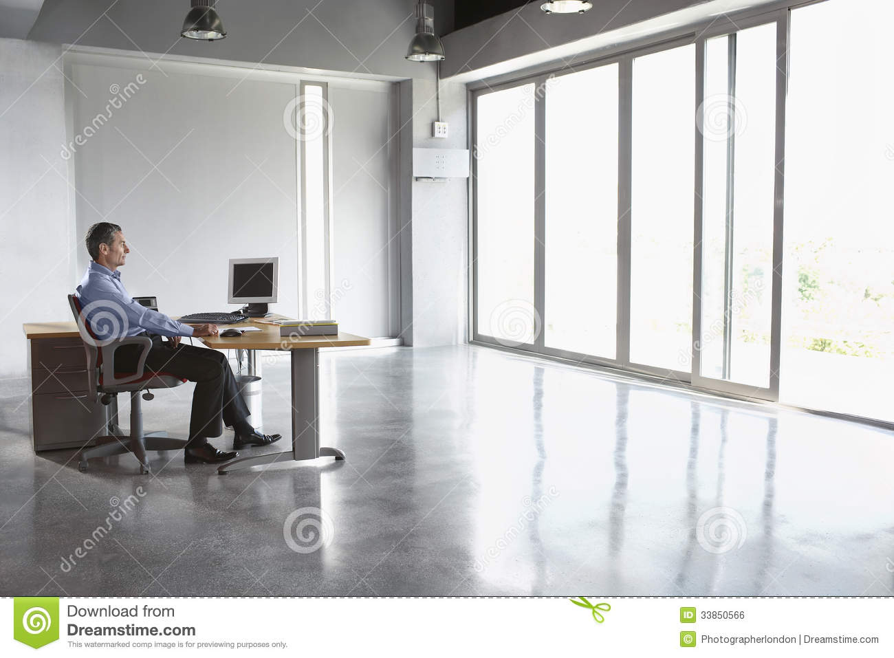 Man Sitting At Desk In Empty Office Royalty Free Stock
