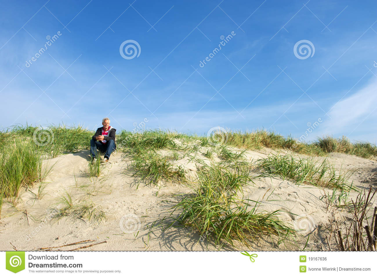 Man is sitting in the dunes