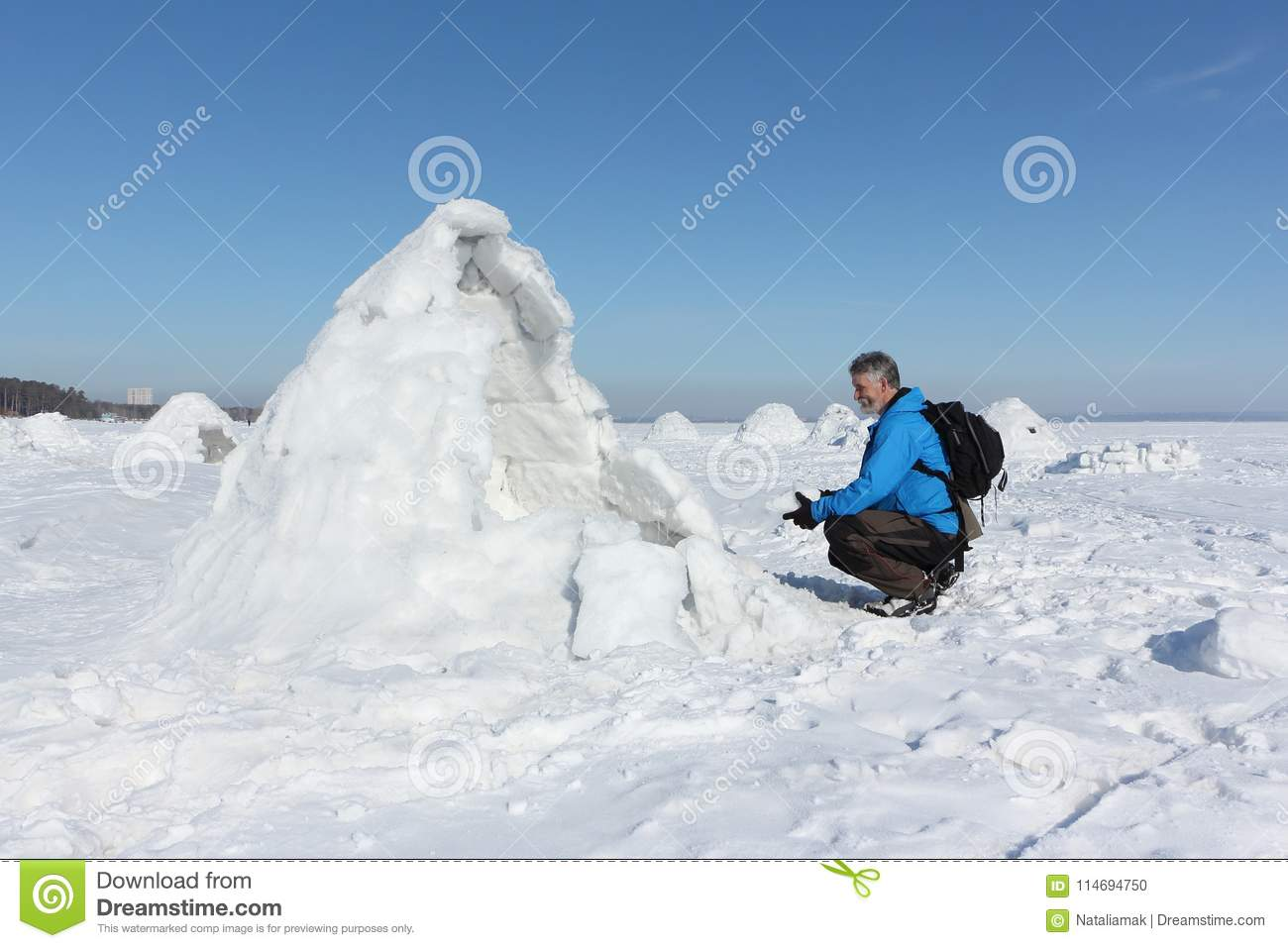 Man sitting at the entrance an igloo in on a snowy reservoir