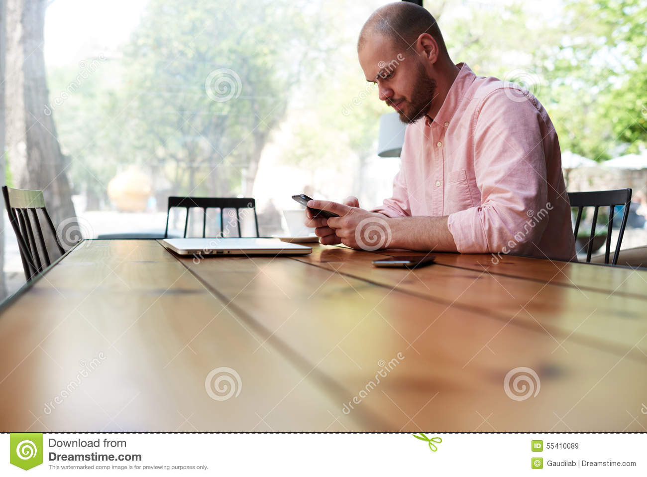 A Man Sitting At A Large Wooden Table In His Hand Phone ...