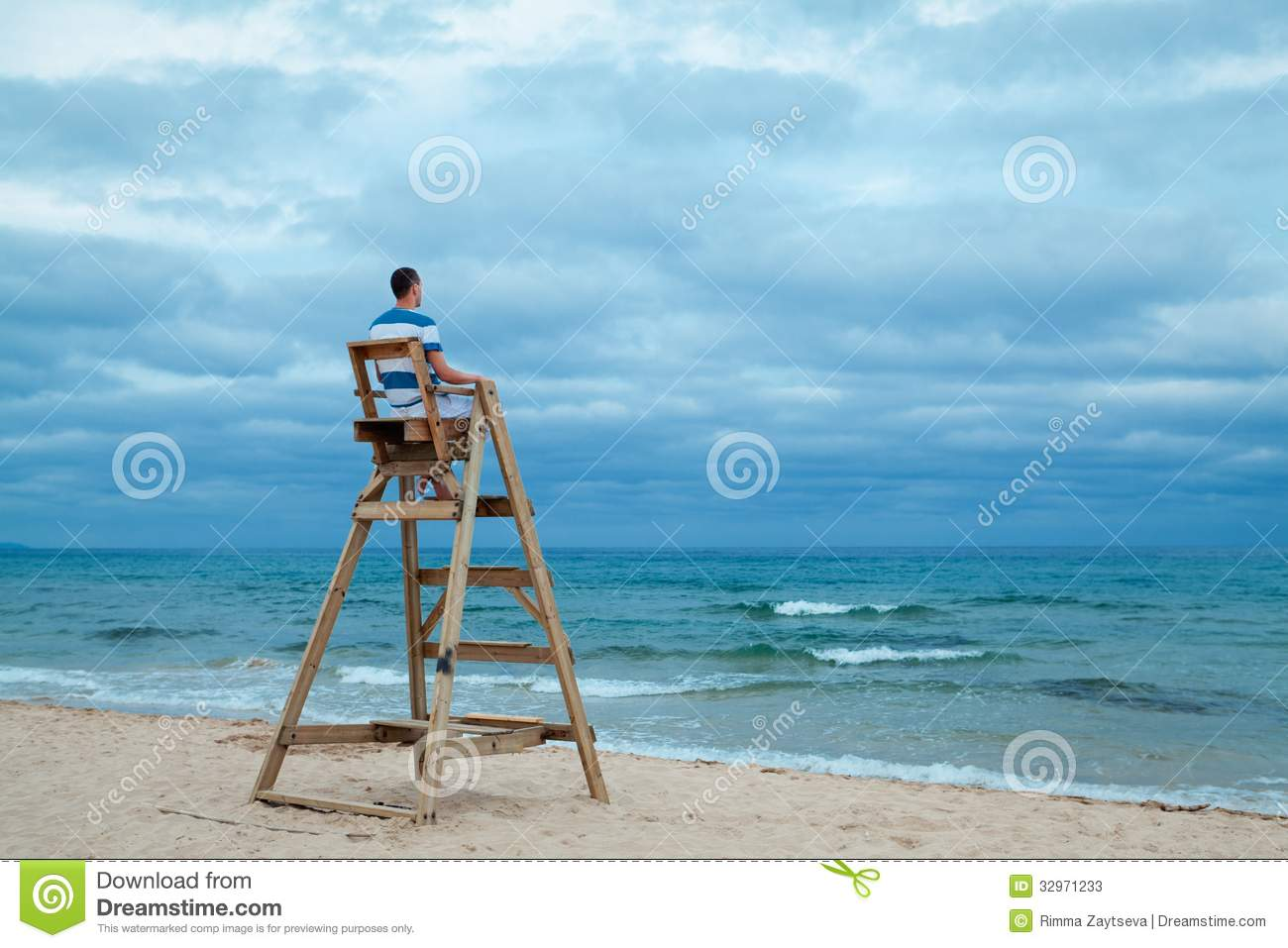 Man sitting on lifeguard chair
