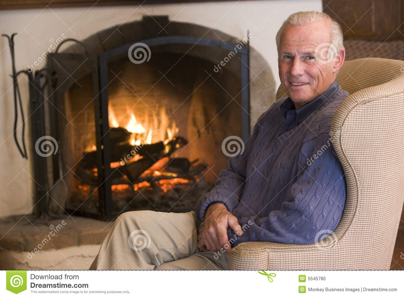 Man Sitting In Living Room By Fireplace Smiling Stock