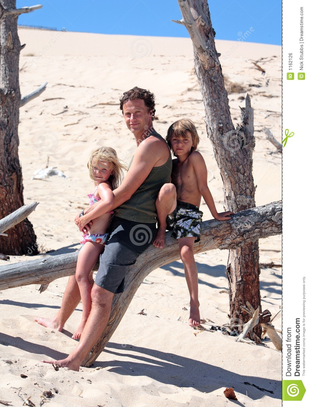 Father sitting on an old tree log with his son and daughter at the beach 541c0911e5c