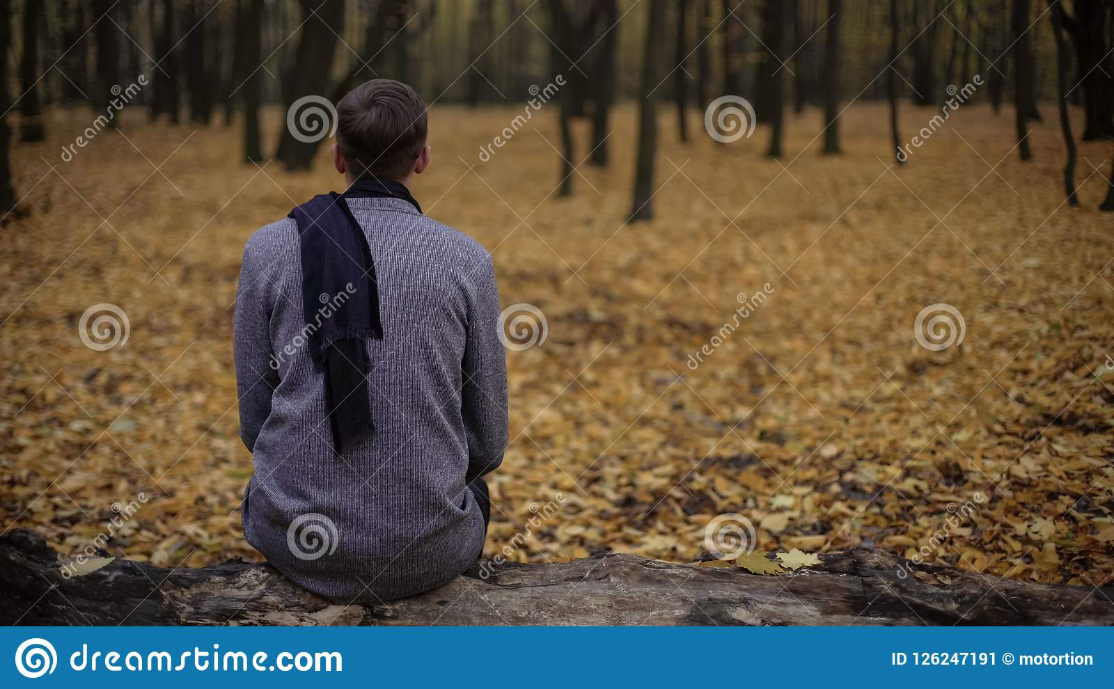 Man sitting in park alone, gray tones express depression, sadness, melancholy