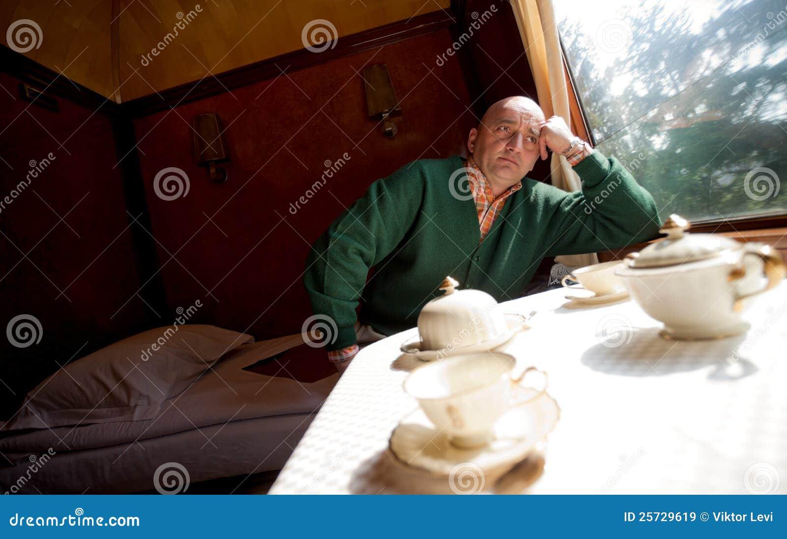 Man sitting sleeping wagon in train