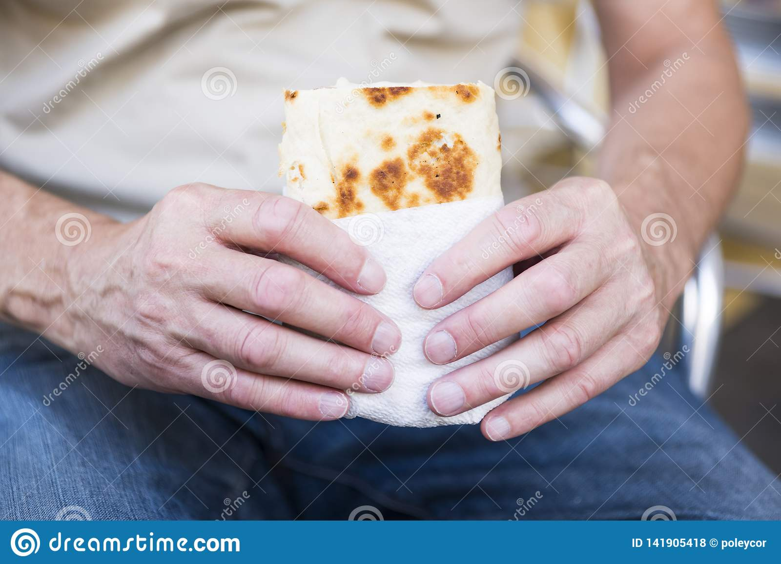 Man holding a wrap, bread, piadina, against white blur background