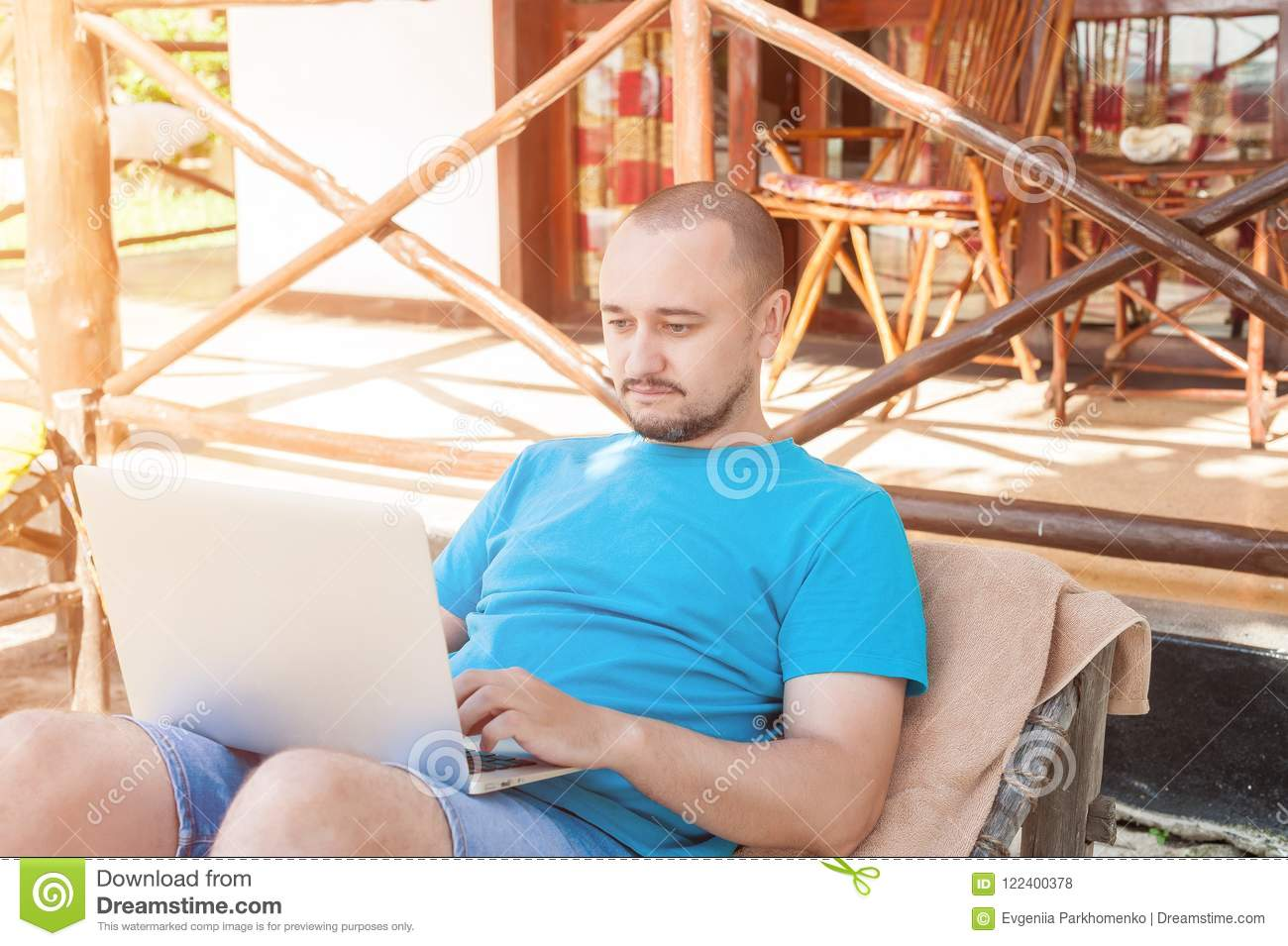 Magnificent A Man Sitting On A Wicker Lounge Chair And Working At The Andrewgaddart Wooden Chair Designs For Living Room Andrewgaddartcom