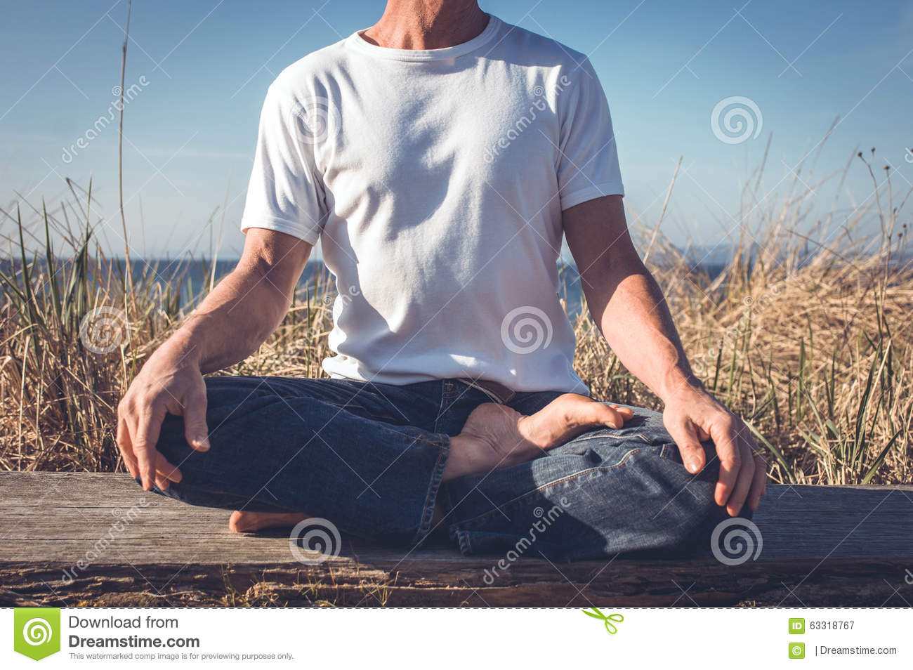 Man sitting in a relaxed yoga pose at the beach. - a