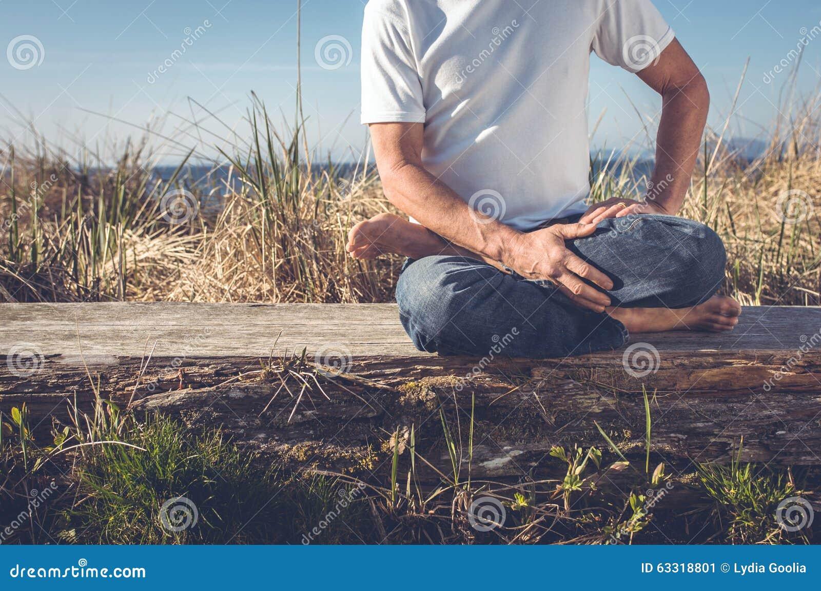 Man sitting in yoga pose. stock photo. Image of mind