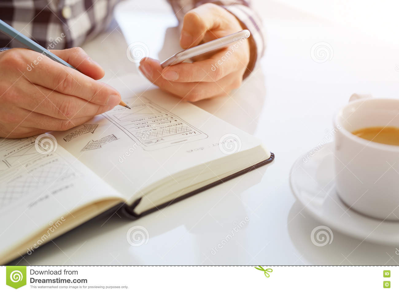 Man sketching web design and holding mobile phone