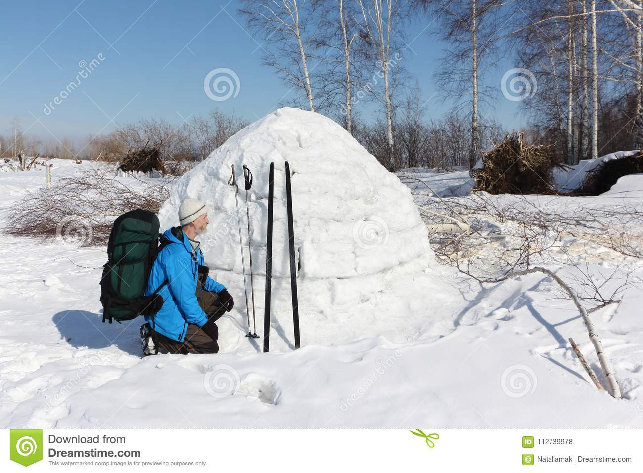Man skier sitting by an igloo on a glade in the winter
