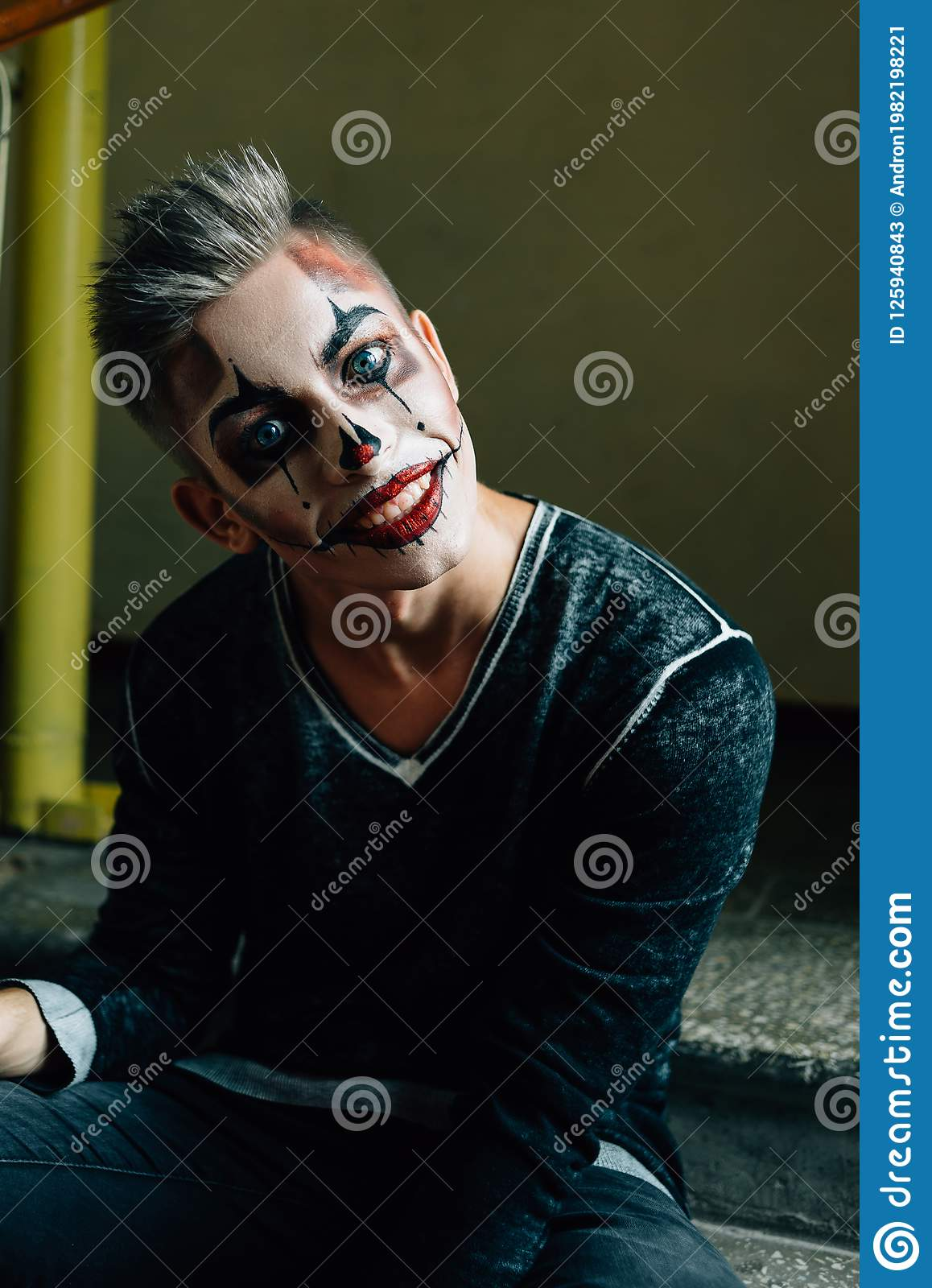 download man with skull makeup in hood looks at camera halloween face art stock image