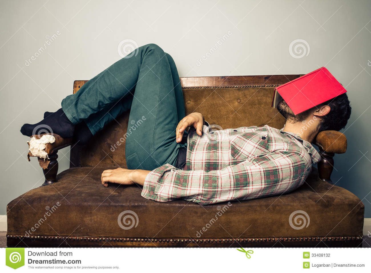 Man sleeping on old sofa with book covering his face stock photo man sleeping on old sofa with book covering his face parisarafo Image collections