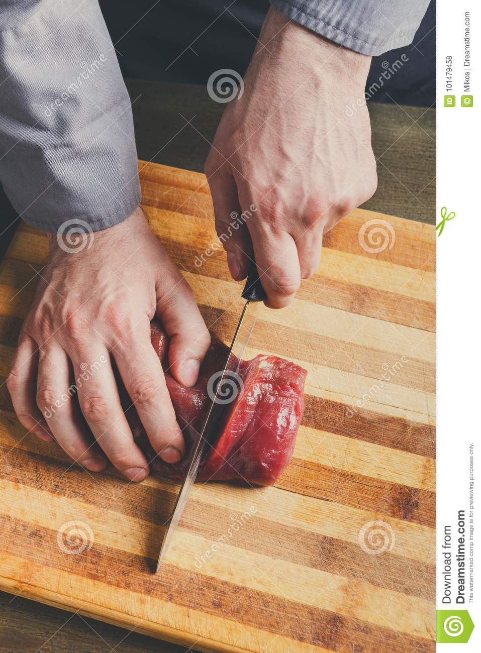 Chef cutting filet mignon on wooden board at restaurant for Fresh chef kitchen