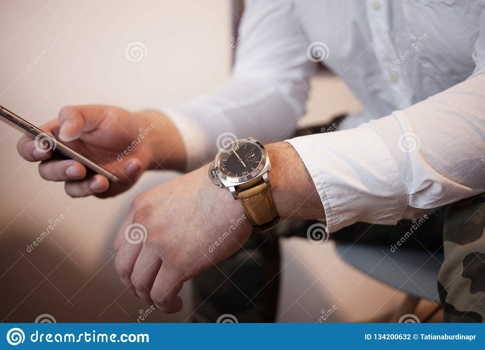 A man with smart phone in a relaxed pose in a white shirt is typing sms psychology and negotiation concept