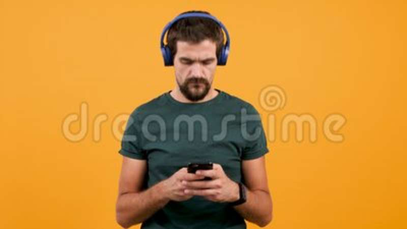 Man With Smartphone In Hands And Headphones On Head Typing And