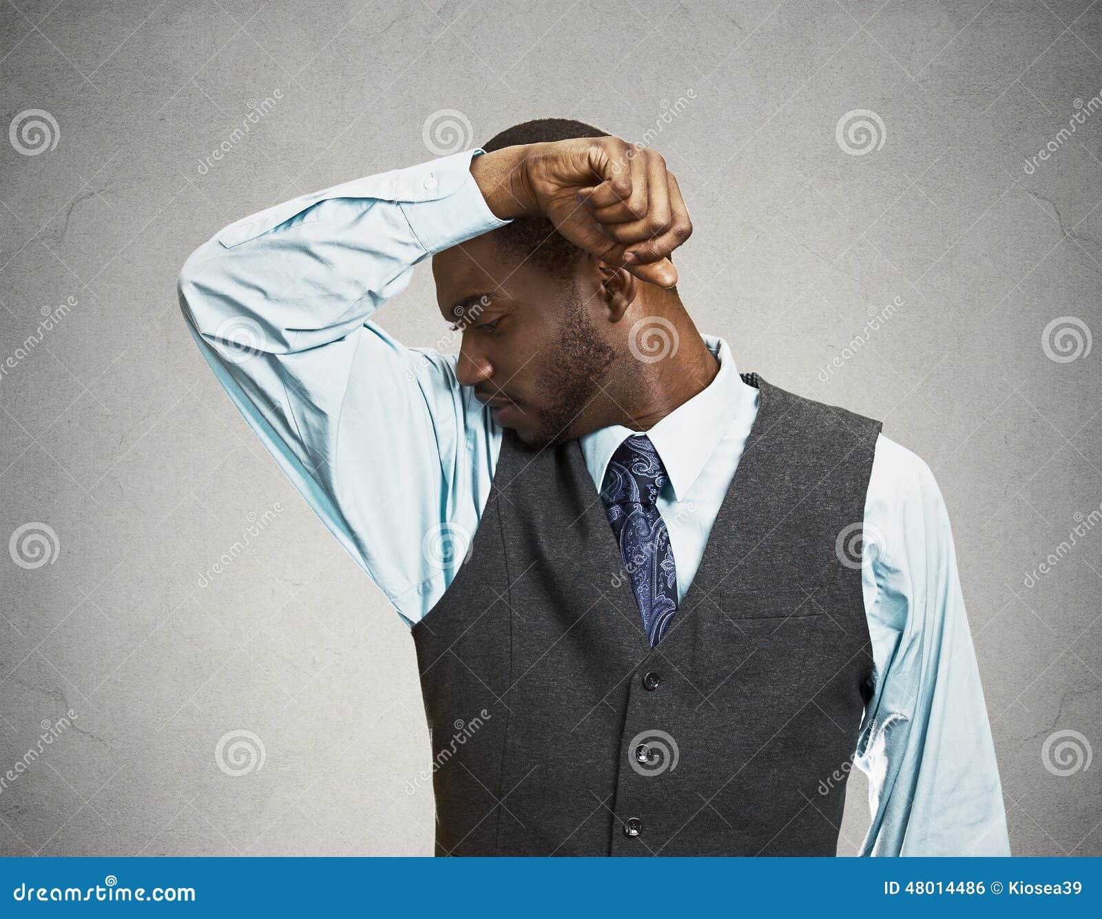 Man smells his armpit, bad odor