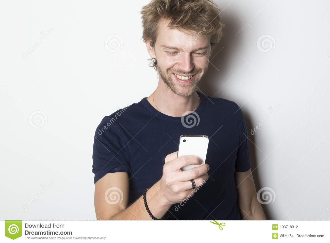Happy young man using his mobile smartphone