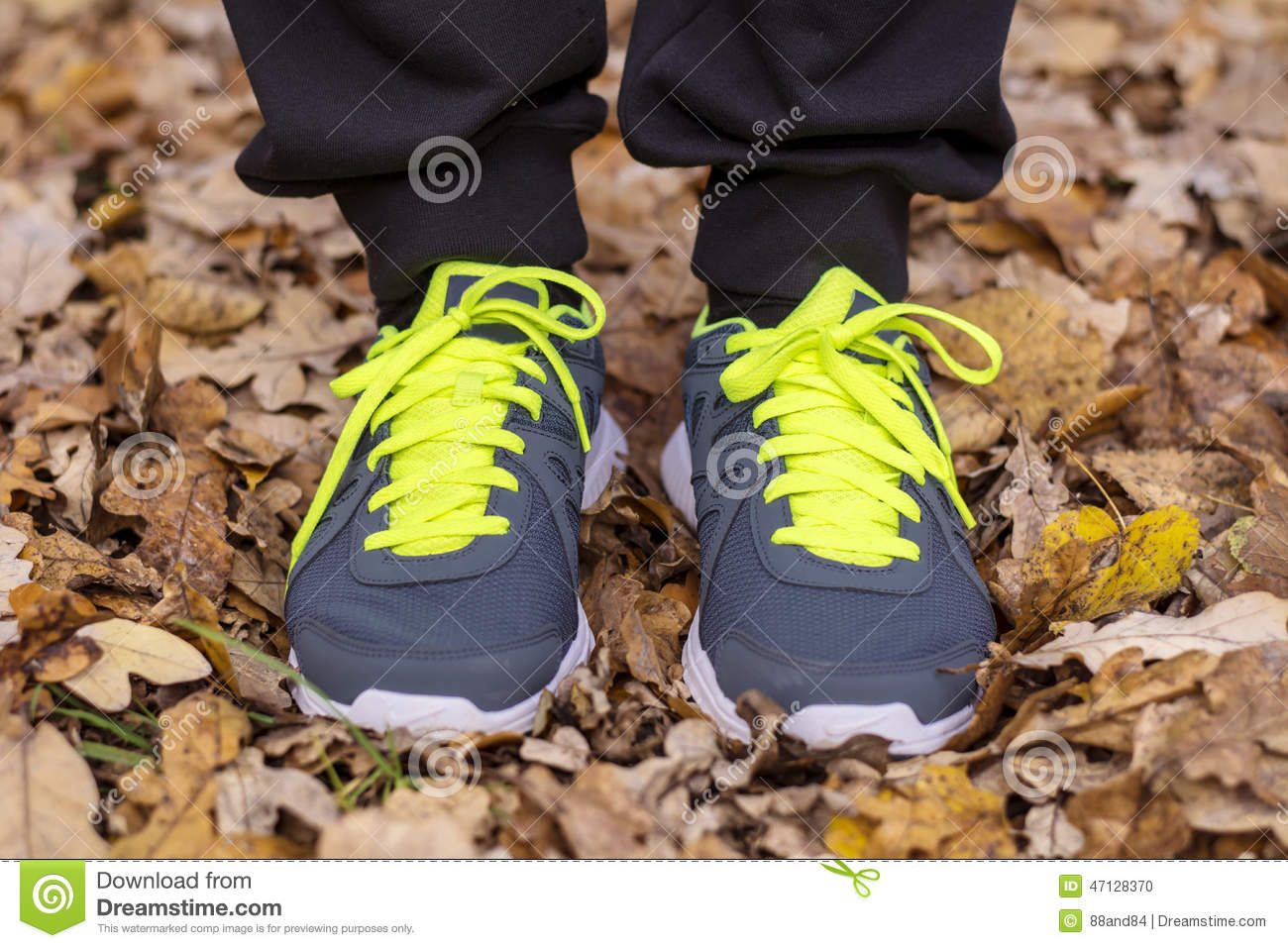 Man with sneakers Standing in dry autumn leaves