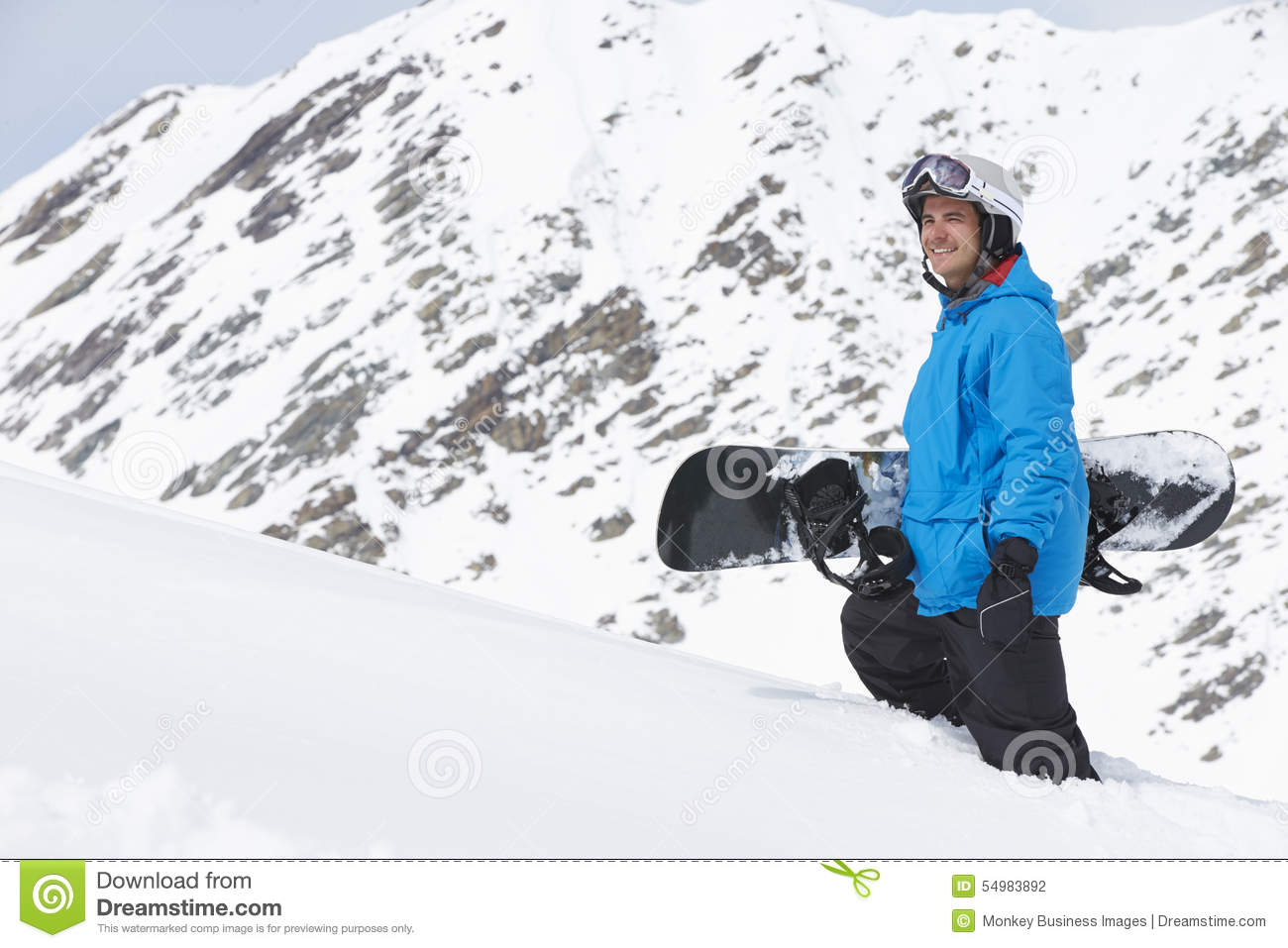 Man With Snowboard On Ski Holiday In Mountains