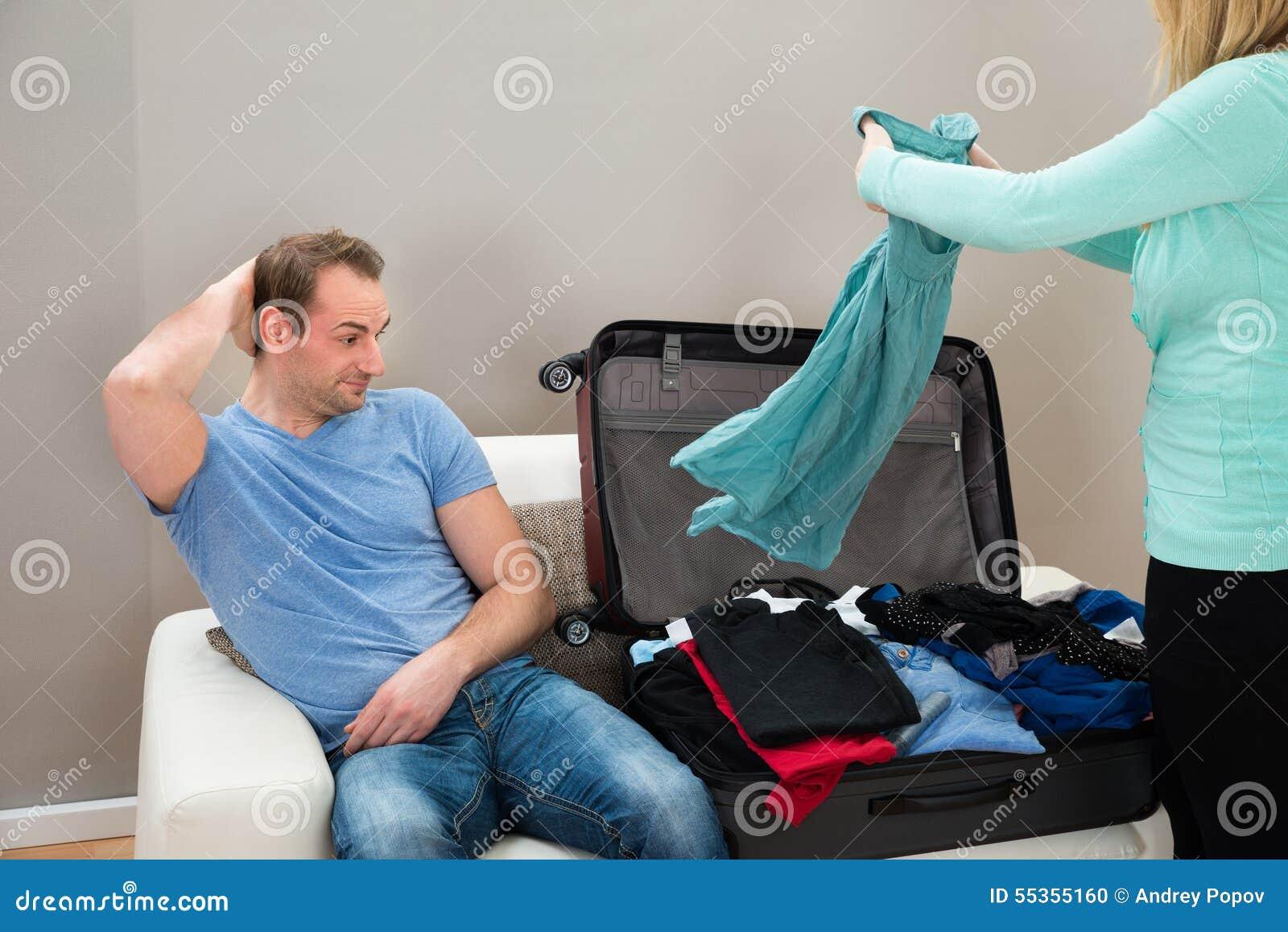 Man on sofa while woman folding clothes