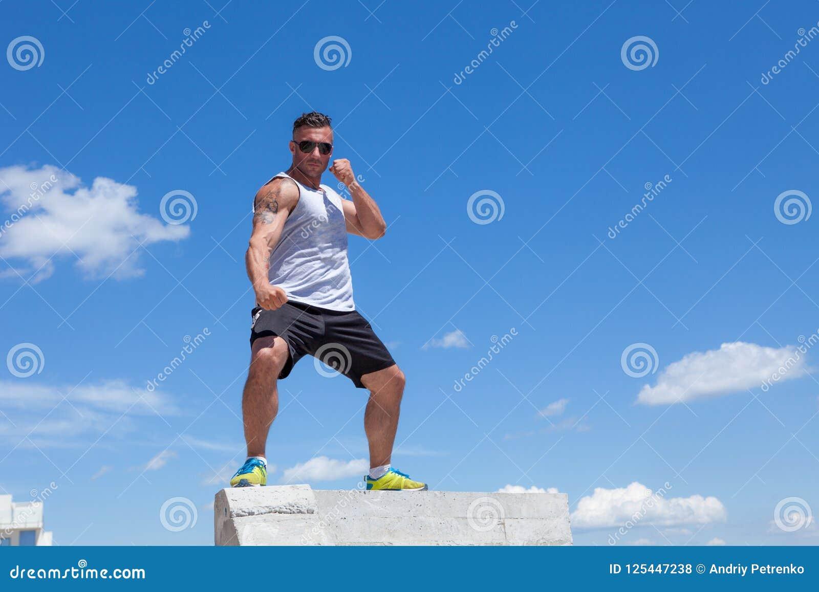 Man som är förlovad i karate mot himlen