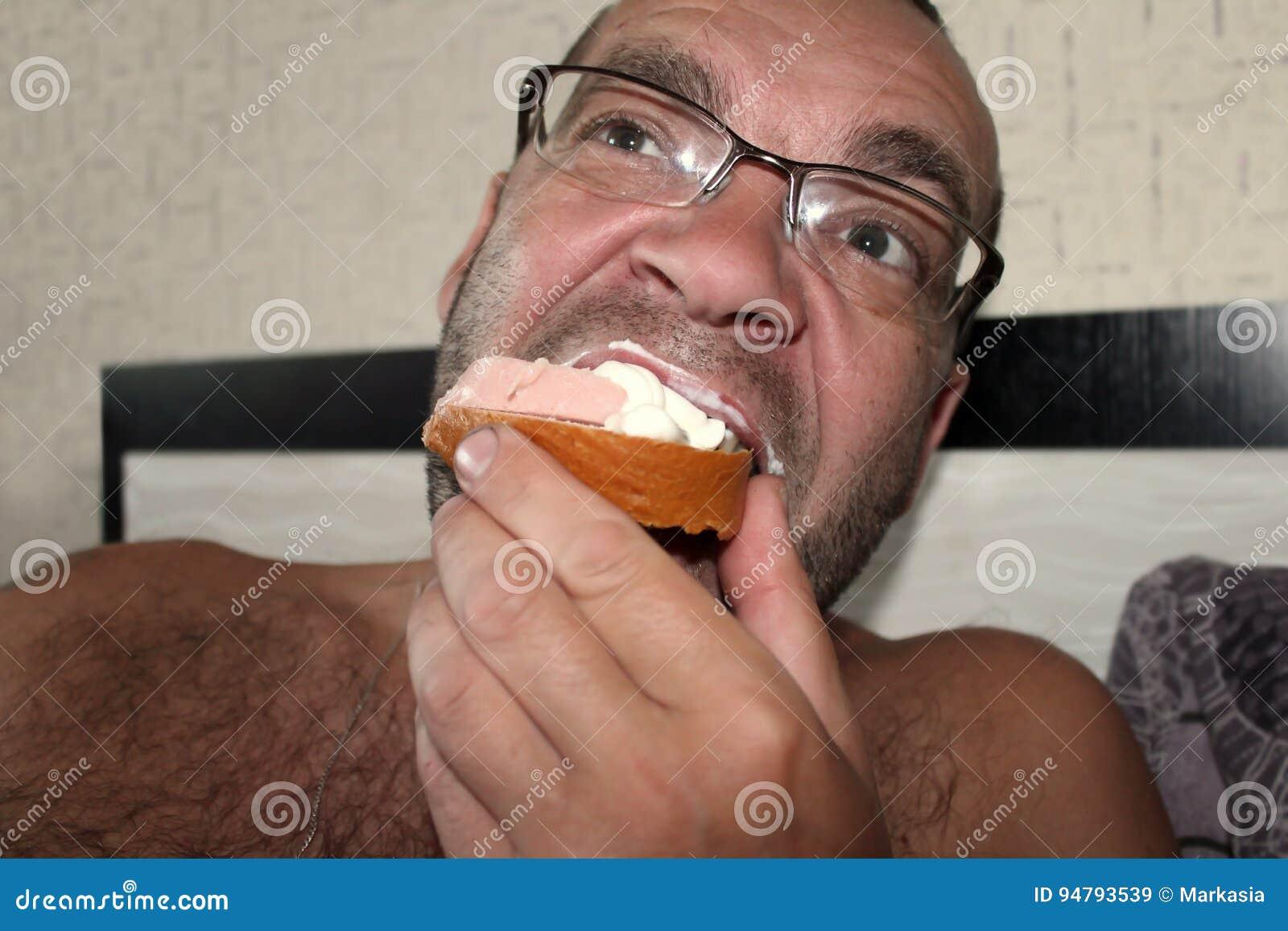 Man som äter en korvsmörgås för matställe